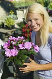 Woman Holding Flowers in plant nursery portrait Stock Image