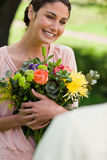 Woman holding flowers which she has been given Royalty Free Stock Photography
