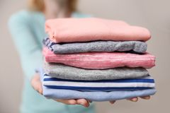 Woman holding folded clothes in hands, Royalty Free Stock Image