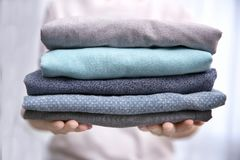 Woman holding folded clothes in hands Stock Image