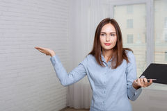 Woman holding a folder expressing bewilderment Royalty Free Stock Photography