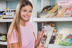 Woman Holding Food Packet In Grocery Store. Portrait of beautiful mid adult woman holding food packet in grocery store royalty free stock photography