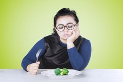 Woman holding fork with broccoli. Portrait of fat woman holding a fork while looking at broccoli on plate Stock Photo