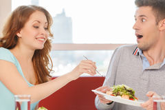 Woman holding fork and eating man's salad. Royalty Free Stock Image