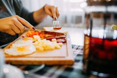 Woman eats breakfast. Eggs and sausages. stock photos