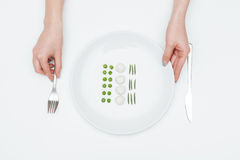 Woman holding fork and plate with green peas, mozzarella, herbs Stock Photo