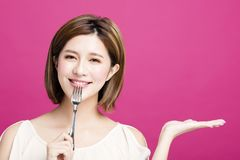 Woman holding fork and showing tasty food. Young woman holding fork and showing tasty food Royalty Free Stock Images