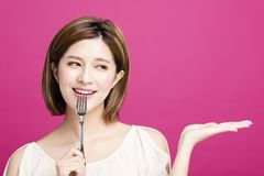 Woman holding fork and showing tasty food. Young woman holding fork and showing tasty food Royalty Free Stock Photography