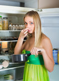 Woman holding foul food near fridge. Girl holding her nose because of bad smell from food near refrigerator at home royalty free stock image