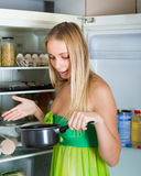 Woman holding foul food near fridge Stock Photography
