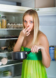 Woman holding foul food near fridge. Young woman holding her nose because of bad smell from food near refrigerator at home royalty free stock images