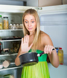 Woman holding foul food near fridge Royalty Free Stock Photos