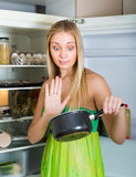 Woman holding foul food near fridge Stock Photo
