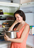 Woman holding foul food near refrigerator Royalty Free Stock Photography