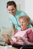 Woman holding frame with picture. Elder disabled women holding frame with picture Stock Image