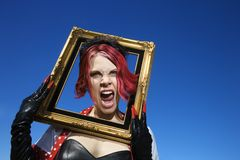 Woman holding framing face screaming. Young adult Caucasian female holding empty frame around head Royalty Free Stock Photography