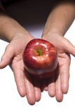 Woman holding fresh apple from dark to light Royalty Free Stock Photos