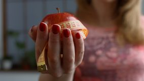 Woman holding fresh apple and measure tape stock footage