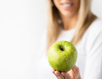Woman holding fresh green apple. Happy woman holding fresh green apple. Healthy life, dieting and nutrition concept Royalty Free Stock Photo