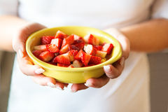 Woman holding fresh strawberries in a bowl Stock Photo