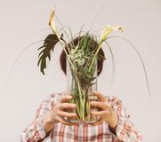 Woman holding in front of her face flower vase with dead plants. Beautiful casual dressed woman hiding her face behind flower vase with two dead cala flower and royalty free stock image