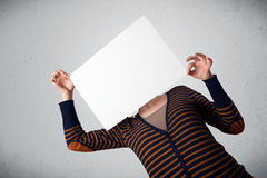 Woman holding in front of her head a paper with copy space Stock Photos