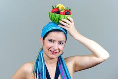 Woman holding fruit bowl over head Royalty Free Stock Photos