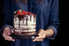 Woman holding a fruit cake, selective focus. A woman in a blue shirt holding a fruit cake Royalty Free Stock Images