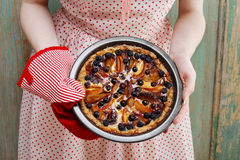 Woman holding fruit tart taken straight out of oven Royalty Free Stock Image