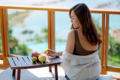 A woman holding fruits while enjoy sitting at balcony with the sea view background. A beautiful asian woman holding fruits while enjoy sitting at balcony with royalty free stock images