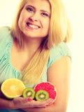Woman holding fruits kiwi. orange, lemon and grapefruit Stock Photos