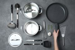 Woman holding frying pan over table with clean cookware. Top view royalty free stock photos