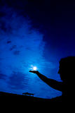 Woman holding full moon in hand against night sky Stock Photos