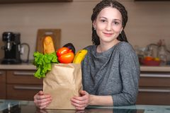 Woman holding full paper bag with products on the background of the kitchen. Fresh organic food for a balanced diet royalty free stock photos