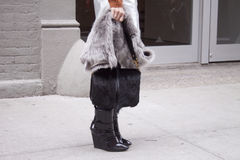 A woman holding a furry black purse and wearing black booties royalty free stock photos