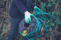 Woman holding garden hose. A woman is holding an old and dirty garden hose outside stock photos