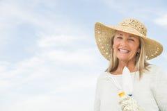 Woman Holding Gardening Equipment Against Sky. Portrait of happy senior woman in sun hat holding gardening equipment against cloudy sky Royalty Free Stock Photo