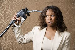 Woman Holding Gas Nozzle to her Head Royalty Free Stock Photo