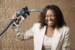 Woman Holding Gas Nozzle to her Head Royalty Free Stock Photography