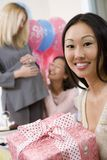Woman Holding Gift At A Baby Shower. Portrait of happy mature women holding gift at a baby shower stock photography