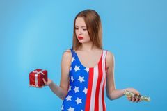 Woman holding a gift box and a bunch of dollar bills and looking at a gift box. On a blue background. A young European brunette woman dressed in bodysuits with Stock Image