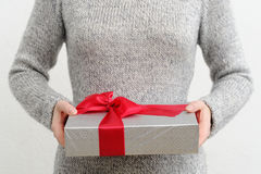 Woman holding gift box, focus on foreground. Stock Photo