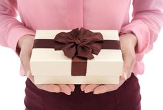 Woman holding gift box in a gesture of giving isolated on white. Woman holding a gift box in a gesture of giving isolated on white background royalty free stock photos