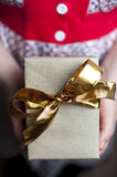 Woman holding gift box with golden ribbon Stock Images