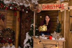 Woman Holding Gift Box at Mini Christmas Booth Stock Photo