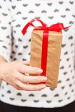 Woman holding a gift box tied with a red ribbon in her hand. Shallow depth of field, Selective focus on the box. Concept of giving a gift on holiday or royalty free stock image