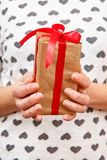 Woman holding a gift box tied with a red ribbon in her hands. Shallow depth of field, Selective focus on the box. Concept of giving a gift on holiday or royalty free stock photos