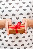 Woman holding a gift box tied with a red ribbon in her hands. Shallow depth of field, Selective focus on the box. Concept of giving a gift on holiday or stock photo