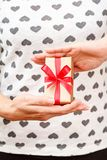 Woman holding a gift box tied with a red ribbon in her hands. Shallow depth of field, Selective focus on the box. Concept of giving a gift on holiday or stock images