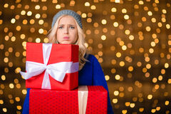 Woman holding gift boxes over holidays lights background. Portrait of a sad woman holding gift boxes over holidays lights background Royalty Free Stock Images